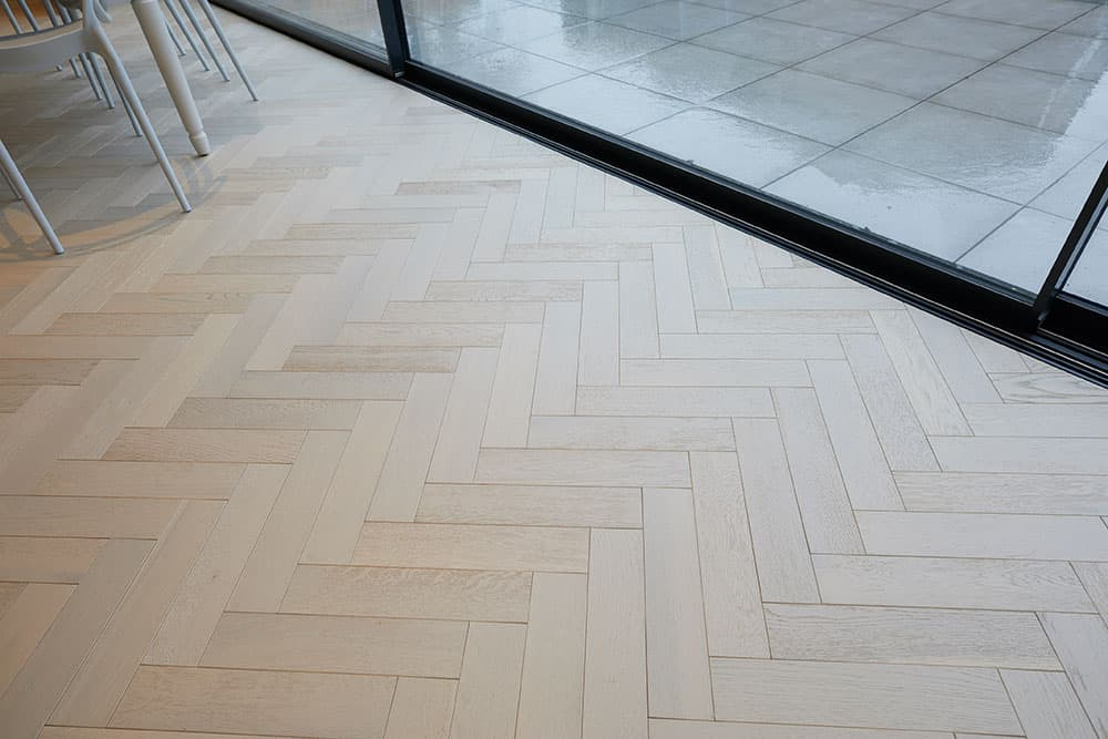 white oak parquet flooring with bifold doors